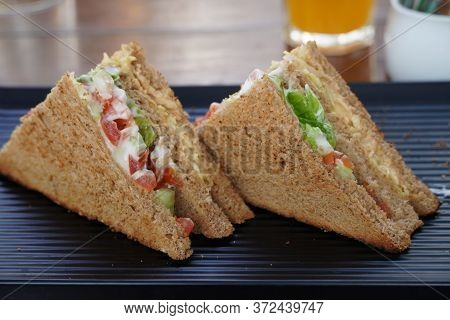 Two Club Sandwiches Placed On A Black Plate At A Restaurant. Close-up Photo Of A Club Sandwich. Sand