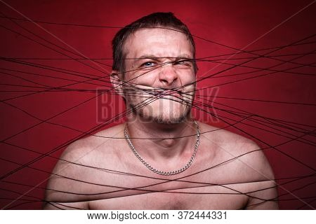 Picture Of Mad Man In Black Threads On Red Background