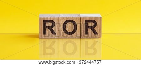 Ror - Rate Of Return. Wooden Blocks With The Word Ror, Yellow Bacground. Concept Image Of Accounting