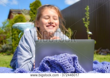 Joyful Girl On Distance Learning. Happy Schoolgirl With The Laptop. Home Schooling Education. Child