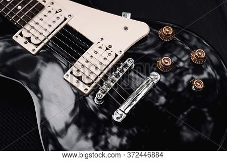 Black And White Electric Bass Guitar. Musical Instrument Close-up. Stylish Still Life With Parts Of