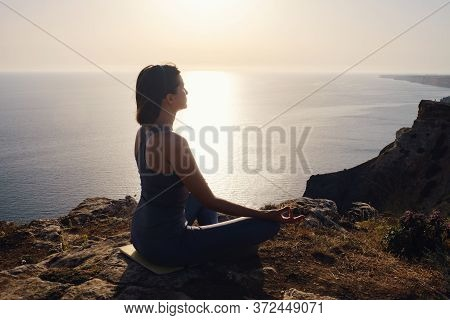Young Woman Practicing Yoga Over Sunset Sea