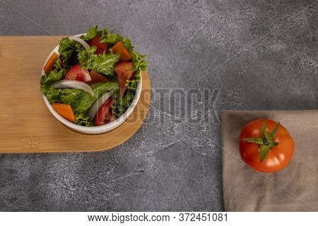 Tomatoes In Salad Inside A White Bowl On Grayish Background