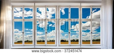 View Of Green, Nature And Blue Sky Background Through Old Window Concept. Retro White Window