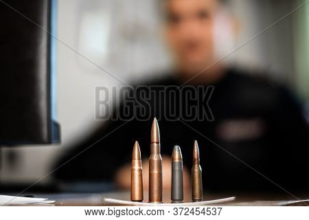 Shells And Bullets Of Various Calibers On The Table At The Detective Investigating The Crime