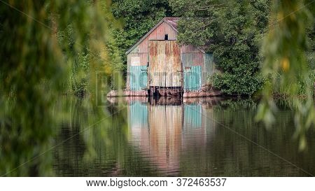 An Old Corrugated Tin Disused Boathouse Surrounded By Trees Standing At The Edge Of Water And Reflec