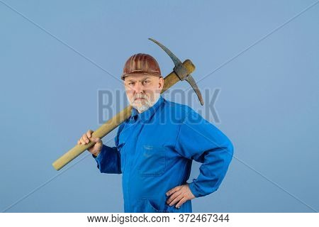 Serious Workman With Pickaxe. Construction Worker With Pick Axe. Male Laborer With Building Tools. M