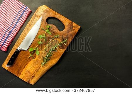 Big Kitchen Knife Lying On An Wooden Cutting Board. Kitchen Utensils. Spices On The Kitchen Board. O