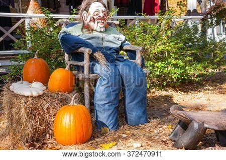 Halloween Mannequin In With Ugly Mask Chair Outside Beside Three Large Orange Pumpkins.