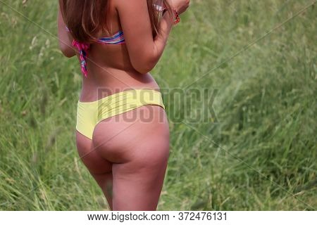Tanned Woman In Yellow Cheeky Shorts Standing On Grass Background, Side View. Concept Of Sunbathing,