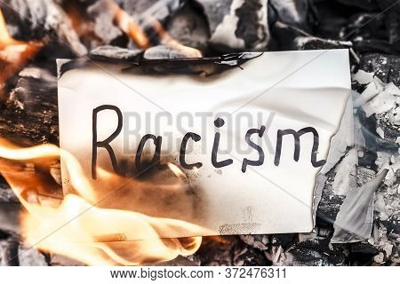 White Paper With Words Racism Burns In Fire. Concept Of Ethnic Conflict And Racial Protest. Idea Of