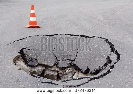 Deep Sinkhole On Street City And Orange Traffic Cone. Dangerous Hole In Asphalt Highway. Road With C