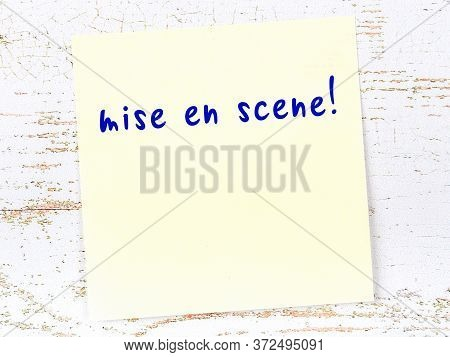 Concept Of Reminder About Mise En Scene. Yellow Sticky Sheet Of Paper On Wooden Wall With Inscriptio