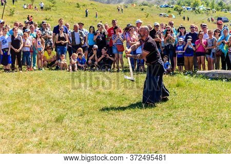 Dnipropetrovsk Region, Ukraine - June 2, 2018: Ukrainian Cossack Performs With Axe During Ethno-rock