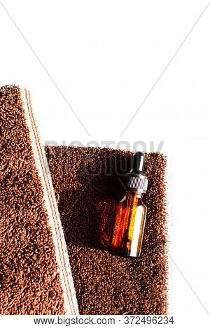 A Brown Colored Towel With An Amber Colored Glass Bottle Placed On It In Strong Sunlight. Background