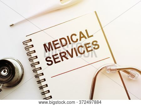 Text Medical Service Write On A Medical Notebook. Background On The White Table With A Stethoscope A