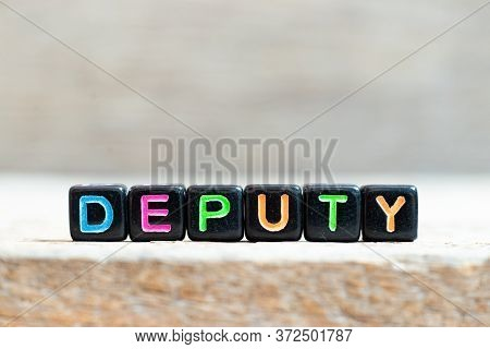 Black Bead With Color Letter In Word Deputy On Wood Background