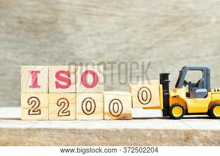 Toy Forklift Hold Letter Block 0 To Complete Word Iso 22000 On Wood Background