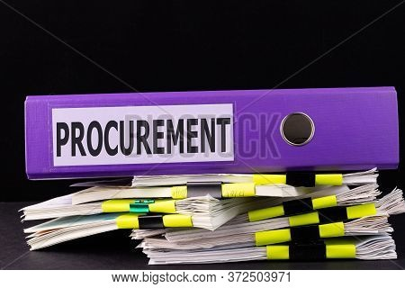 Text Procurement Is Written On A Folder Lying On A Stack Of Papers On A Table. Business Concept