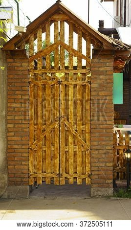 Original Brown Wooden Door To Enter The Backyard.property With Landscape Gardening And Backyard