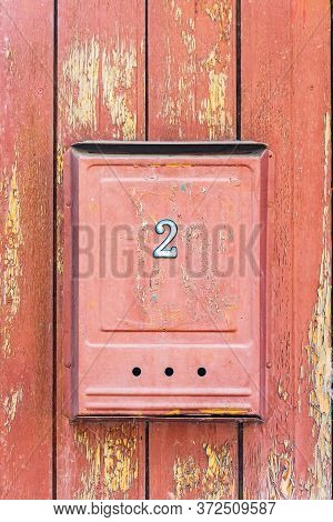 Red Mailbox With Number 2 On A Red Wooden Wall Close Up