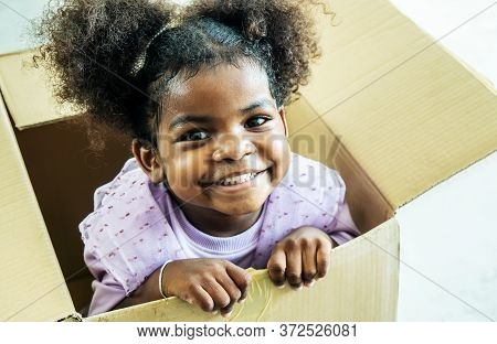 Happy Cute Active Little African American Kids Girl Play Riding In Cardboard Boxes Feel Excited To M