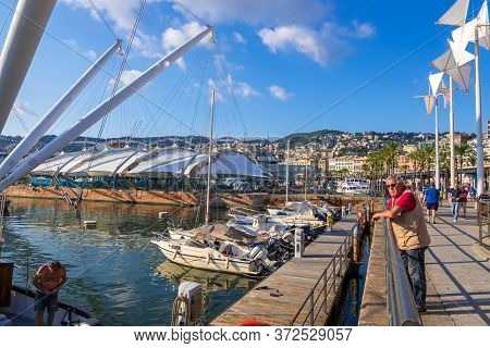 Genoa, Italy - August 18, 2019: Tourists And Locals Walk Along The Promenade In Porto Antico Di Geno