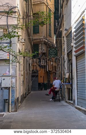 Genoa, Italy - August 20, 2019: Typical Narrow Street Of Genoa With The Sidewalk Cafes, Shops And Mu