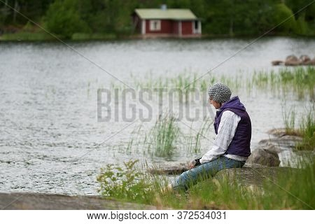 Young Woman Wearing Hat And Purple Waistcoat Relaxing On Lakeside In Breezy Summer Day.