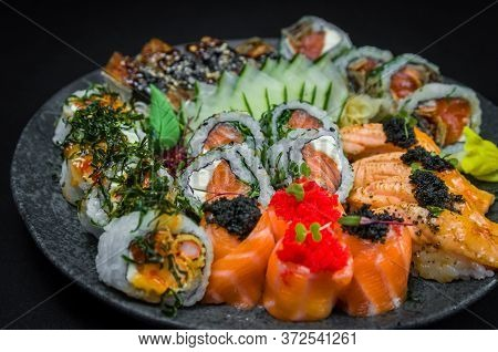 Sushi, Traditional Japanese Cuisine. Several Delicious Sushi On The Decorated Plate, Black Backgroun
