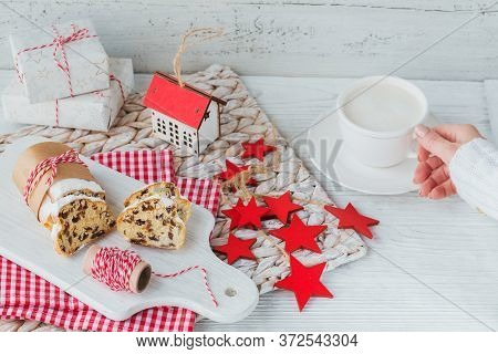 Christmas Stollen Sliced On A White Wooden Table. Stollen For Christmas. Female Hand In Warm Sweater