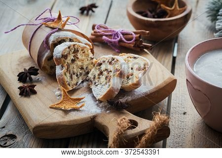 Christmas Stollen Sliced On A Wooden Board With Cinnamon Stick And Anise Stars. Stollen For Christma