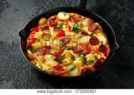 Frittata Made Of Eggs, Potato, Chorizo, Red Bell Pepper And Greens In Iron Cast Pan