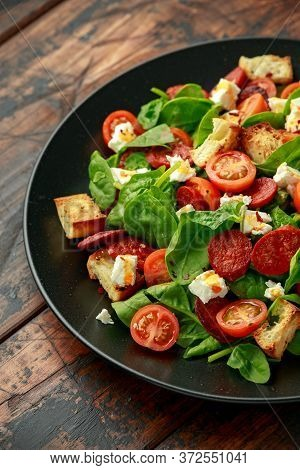 Chorizo Tomato Salad With Spinach, Feta Cheese And Croutons On Black Plate. Healthy Summer Food