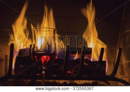 Burning Firewood In A Home Fireplace, A Glass Of Vine, Bright Flames, A Symbol Of Warmth And Comfort
