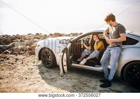 Romantic Couple Is Standing Near A Muscle Car On The Beach. The Handsome Bearded Man And An Attracti