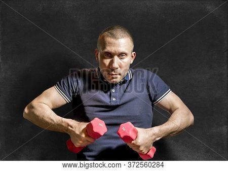 A Stern Man Holds Dumbbells In His Hands Against The Background Of A Chalkboard.