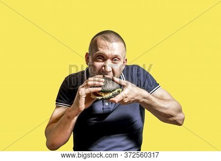 A Hungry Man Enjoys Eating A Black Burger On A Yellow Background .