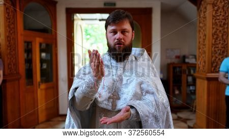 The Sacrament Of Baptism. Priest Holding Ceremony Of Orthodoxal Christening The Baby In Chirch