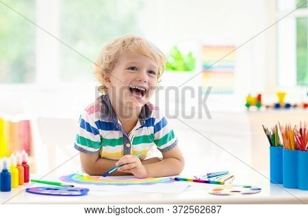 Kids Paint. Child Painting In White Sunny Study Room. Little Boy Drawing Rainbow. School Kid Doing A