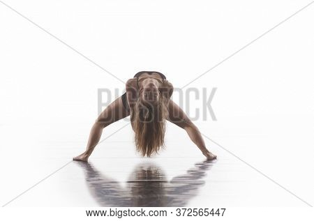 young beautiful female sporty dancer in black tights performing modern style ballet making acrobatic elements   female ballet dancer in art performance in front of white background