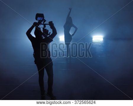 Professional videographer with gimball video slr recording video of female athletic dancer  while performing modern style ballet making acrobatic elements in a dark environment