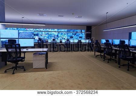 Empty interior of big modern security system control room, workstation with multiple displays, monitoring room with at security data center  Empty office, desk, and chairs at a main CCT security data
