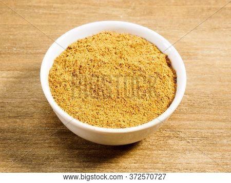 Spice Masala Powder In White Bowl On Brown Wood Background. Healthy Eating, Ayurveda, Naturopathy Co