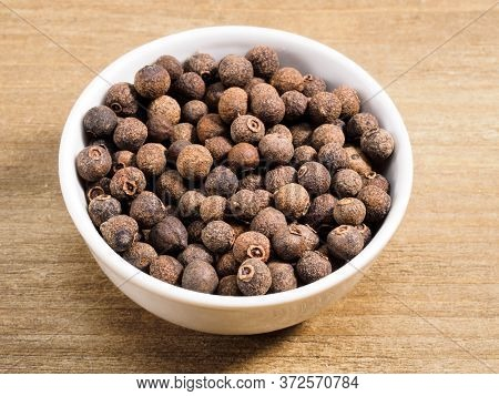 Spice Allspice In White Bowl On Brown Wood Background. Healthy Eating, Ayurveda, Naturopathy Concept