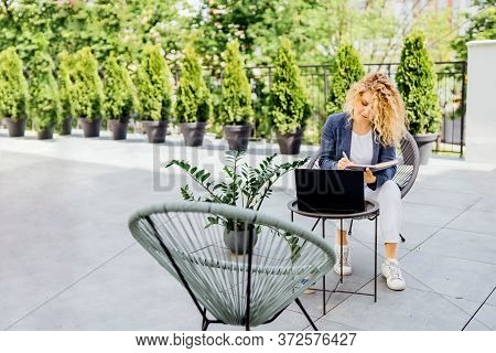 Successful Positive Blond Business Woman Is Sitting On An Outdoor Terrace With A Notebook In A Sun L