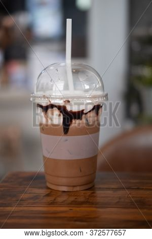 Iced Mocha In Take Away Plastic Cup Put On Wood Table At Coffee Shop