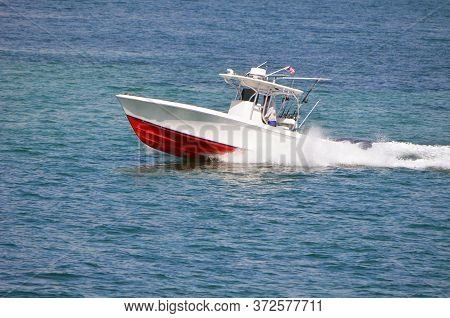 White Sport Fishing Boat With Red Trim Powered By Two Outboard Engines Speeding On The Florida Intra