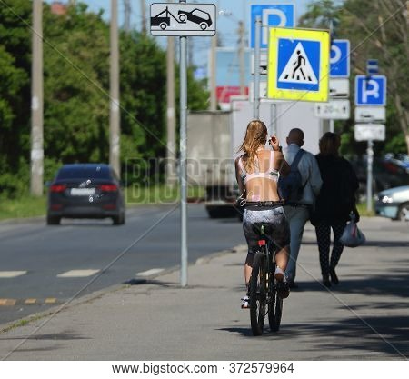 A Girl On A Bicycle Rides On The Sidewalk, Prospect Bolsheviks, St. Petersburg, Russia June 2020