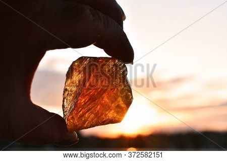 An Silhouette Image Of A Hand Holding A Piece Of Hone Calcite Against A Glowing Sunset.